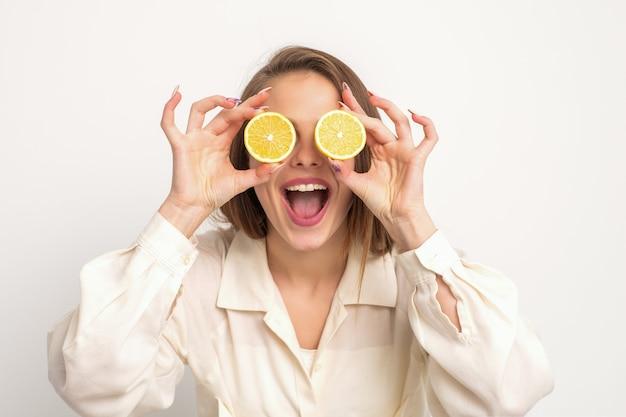 Portret van een mooie jonge vrouw met een open mond die twee plakjes sinaasappel tegen haar ogen houdt