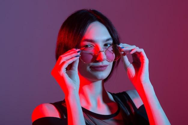 Portret van een mooie jonge vrouw met gekleurde verlichting in zonnebril
