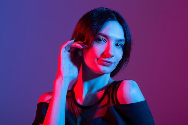 Portret van een mooie jonge vrouw met gekleurde verlichting