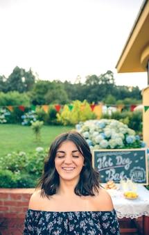 Portret van een mooie jonge vrouw met gesloten ogen die lacht voor een tafel en een tuin in een zomerbarbecue in de buitenlucht