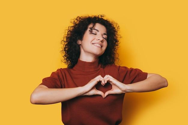 Portret van een mooie jonge vrouw met krullend haar geïsoleerd op gele achtergrond lachend met gesloten ogen terwijl het tonen van liefde met haar handen.