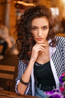 Portret van een mooie jonge vrouw met krullende haarclose-up