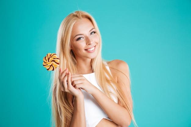 Portret van een mooie jonge vrouw met lang haar die lolly vasthoudt en naar camera kijkt die op de blauwe achtergrond is geïsoleerd