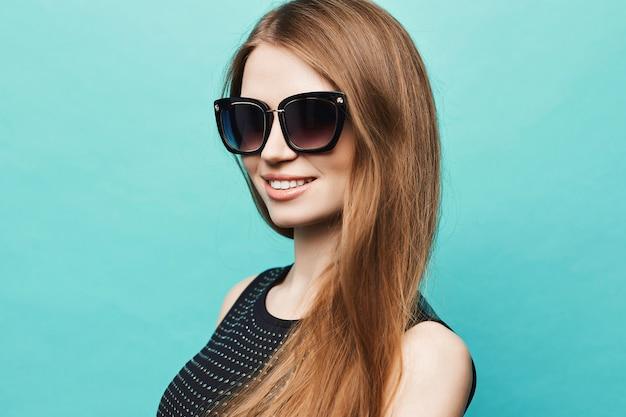 Portret van een mooie jonge vrouw met lang haar en een perfecte gladde huid in een zwart t-shirt en modieuze zonnebril geïsoleerd op lichtblauw. jonge lachende vrouw in een trendy outfit