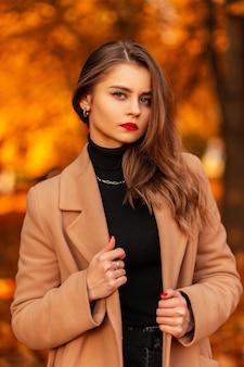 Portret van een mooie jonge vrouw met rode lippen in een modieuze beige jas met een trui in een park met gekleurd geel herfstgebladerte. vrouwelijke casual stijl en schoonheid