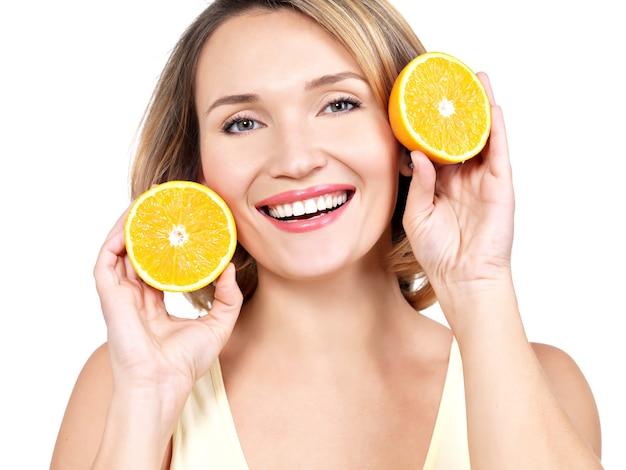 Portret van een mooie jonge vrouw met sinaasappelen op wit wordt geïsoleerd.