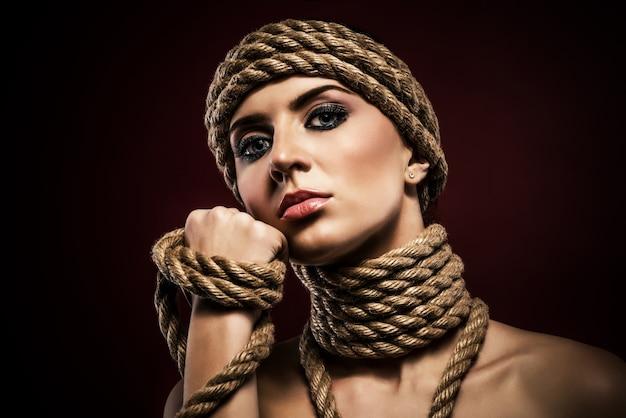 Portret van een mooie jonge vrouw met touwen vastgebonden op haar hoofd en nek. mode en couture concept. advertentie ruimte