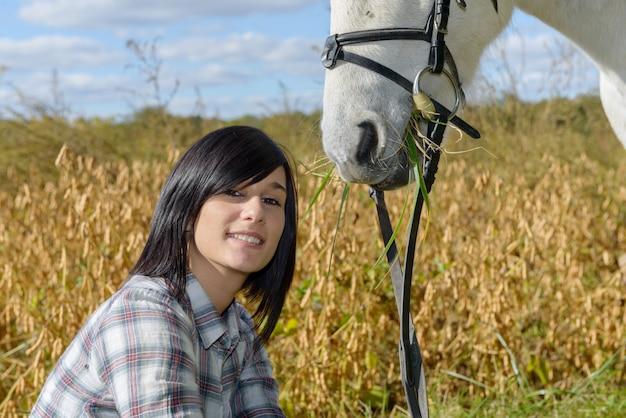 Portret van een mooie jonge vrouw met wit paardrijden