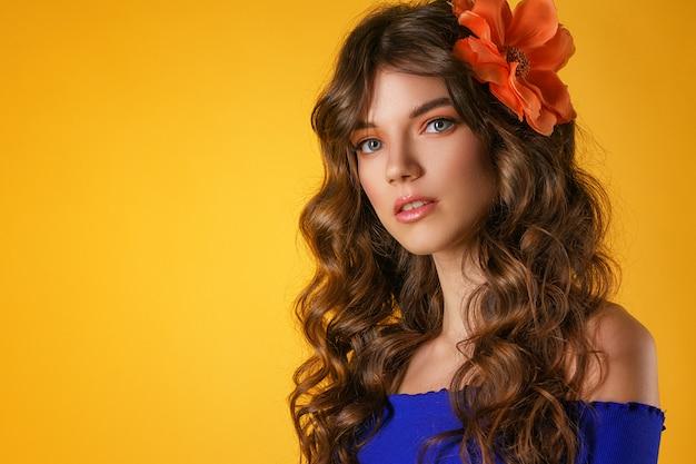 Portret van een mooie jonge vrouw op een gele achtergrond,