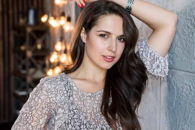 Portret van een mooie jonge vrouw tegen decoratief licht