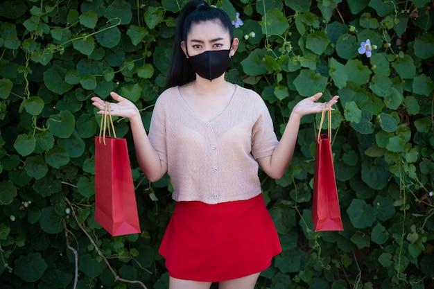 Portret van een mooie jonge vrouw van azië die een gezichtsmasker draagt met boodschappentassen op de achtergrond van de bladmuur, vrouwen dragen roze kleding en rode rok kijken naar de camera