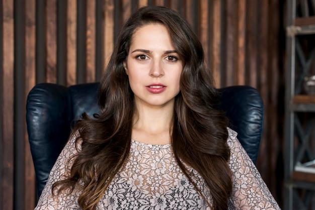 Portret van een mooie jonge vrouw zittend op fauteuil camera kijken