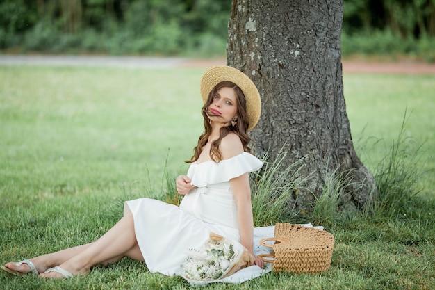 Portret van een mooie jonge zwangere vrouw in de natuur