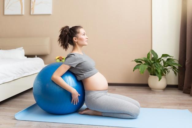 Portret van een mooie jonge zwangere vrouw oefent met blauwe fitball in de huiskamer