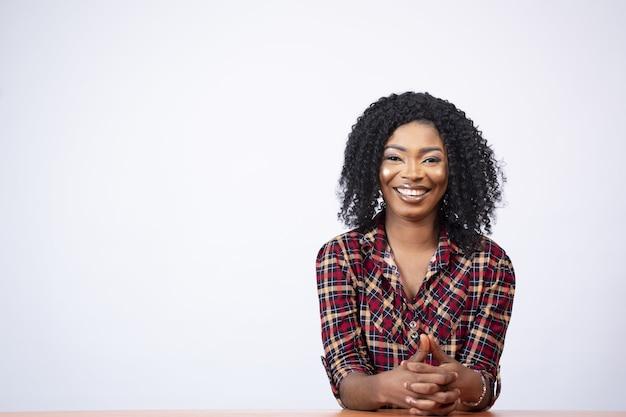 Portret van een mooie jonge zwarte vrouw die aan een bureau zit