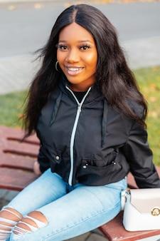 Portret van een mooie jonge zwarte vrouw met een glimlach in een modieus casual jasje met spijkerbroek en een tas zit op een parkbank