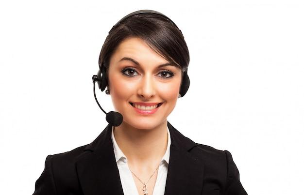 Portret van een mooie klantenvertegenwoordiger die op wit wordt geïsoleerd