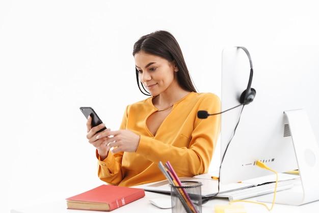 Portret van een mooie klantondersteunende vrouw met microfoonheadset die smartphone vasthoudt terwijl ze in een callcenter werkt
