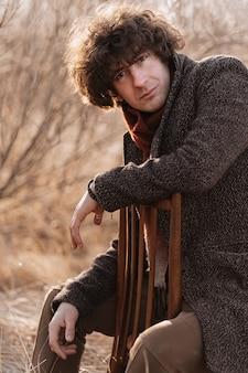 Portret van een mooie krullende jonge man in de natuur op een stoel