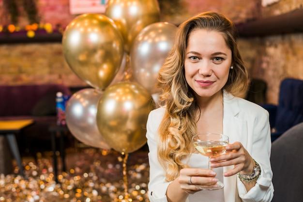 Portret van een mooie lachende vrouw met een glas whisky in de partij
