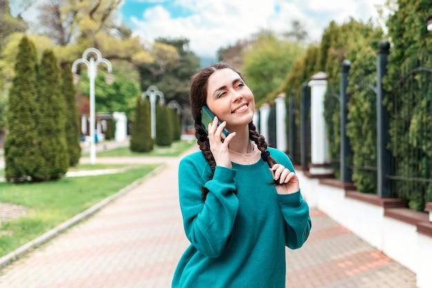 Portret van een mooie lachende vrouw met staartjes praten aan de telefoon. op de achtergrond is er een steegje met bomen. communicatieconcept.