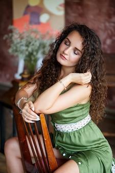 Portret van een mooie lachende vrouw van europees uiterlijk in een jurk met krullen kapsel. mode en schoonheid