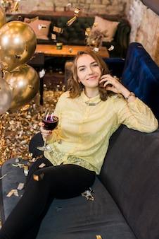 Portret van een mooie lachende vrouw zittend op de bank met een glas wijn