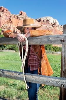 Portret van een mooie langharige blonde jonge vrouw die een cowboyhoed draagt