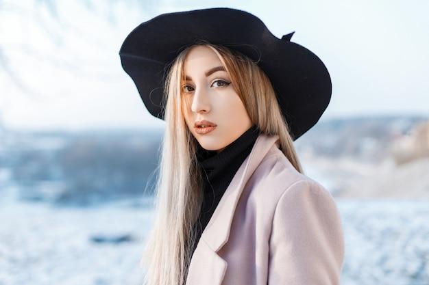 Portret van een mooie leuke vrouw met natuurlijke make-up met schone huid in een stijlvolle elegante hoed in een roze jas in een vintage gebreide golf. sensueel meisje. detailopname.