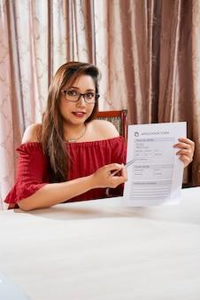 Portret van een mooie manager van een makelaar die uitlegt welke persoonlijke gegevens in het aanvraagformulier moeten worden geschreven
