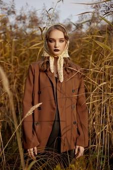 Portret van een mooie maniervrouw in een struikgewas van de herfstgras