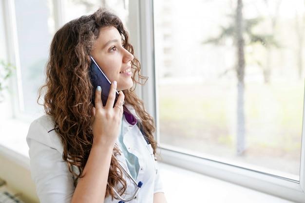 Portret van een mooie medische arts die op de telefoon spreekt. medische concept