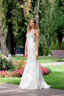 Portret van een mooie modebruid in park. bruiloft make-up en haar.