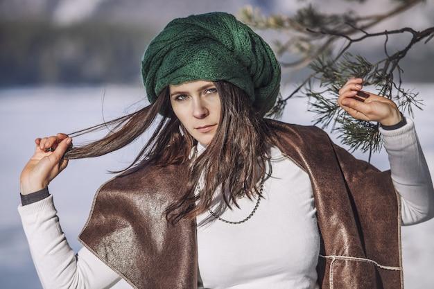 Portret van een mooie modieuze jonge vrouw in de winter met een tak van een boom in een hoofdtooi