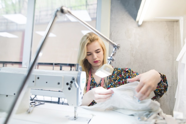 Portret van een mooie naaister op de werkplek in de buurt van een naaimachine.