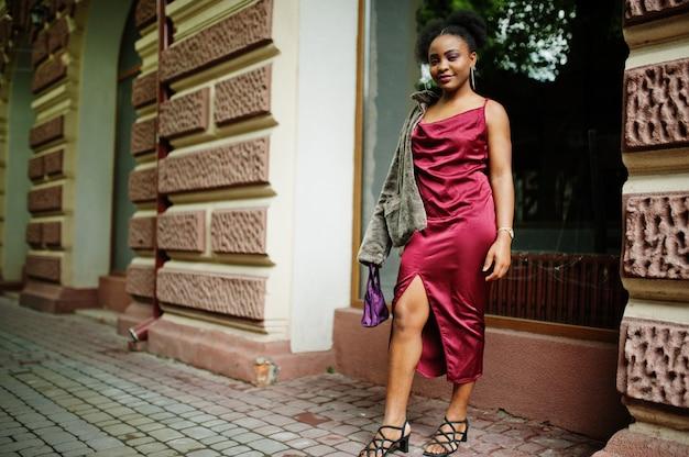 Portret van een mooie natuurlijke jonge afrikaanse vrouw met afrohaar. zwart model in rode zijden jurk.