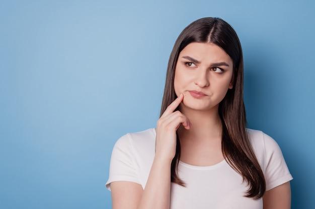 Portret van een mooie, onzekere dame kijkt lege ruimtevingerwang op blauwe achtergrond