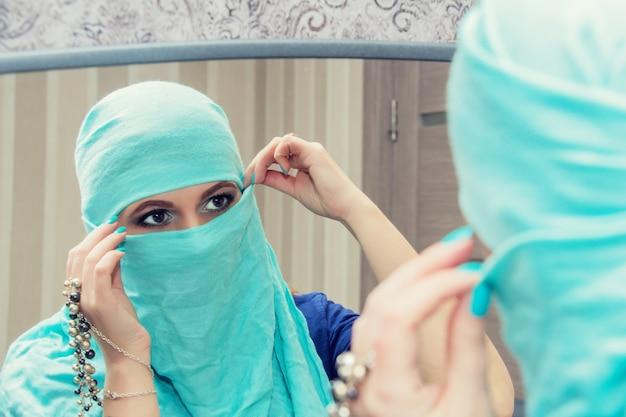 Portret van een mooie oosterse vrouw in niqab, de weerspiegeling in de spiegel.