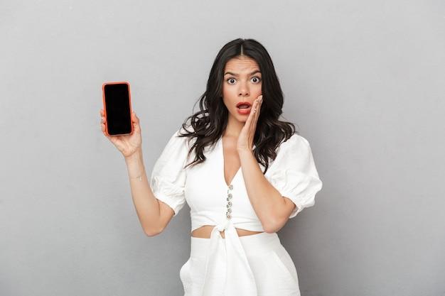 Portret van een mooie opgewonden jonge brunette vrouw met een zomeroutfit die geïsoleerd staat over een grijze muur en een mobiele telefoon met een leeg scherm toont