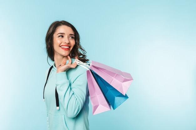 Portret van een mooie opgewonden jonge brunette vrouw permanent over blauw, met boodschappentassen