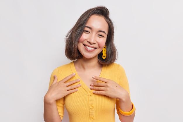 Portret van een mooie oprechte aziatische vrouw met donker haar kantelt het hoofd voelt zich gelukkig, voelt zich blij dat ze een gele trui draagt die over een witte muur is geïsoleerd