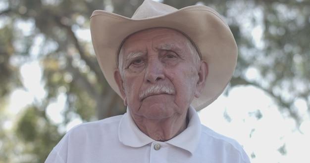 Portret van een mooie oudere man in het zomerpark op zoek naar de camera, hoop en vertrouwen.