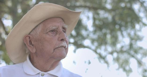 Portret van een mooie oudere man in het zomerpark op zoek naar de horizon, hoop en vertrouwen.