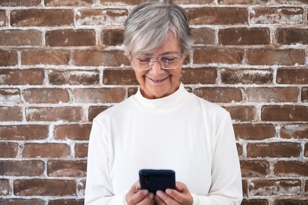 Portret van een mooie oudere vrouw met wit haar die een telefoon gebruikt die tegen een bakstenen muur staat te glimlachen