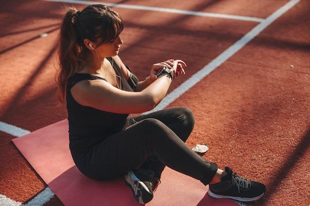 Portret van een mooie plus size vrouw zittend op de grond rusten en kijken naar haar sporthorloge na het doen van cardio buiten in een sportpark.
