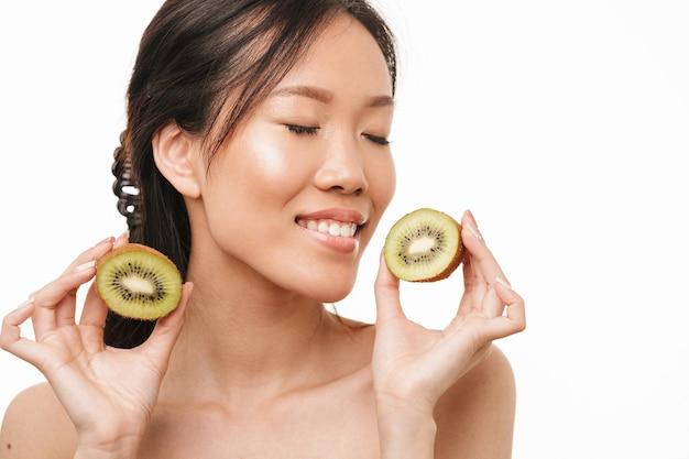 Portret van een mooie positieve aziatische jonge mooie vrouw met een gezonde huid poseren geïsoleerd over een witte muur met kiwi
