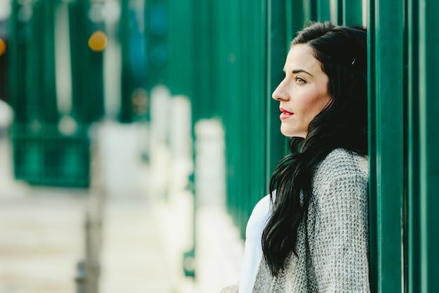 Portret van een mooie rijpe donkerbruine vrouw op straat die met zijdelings starende blik kijkt