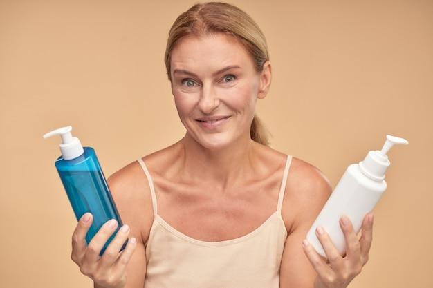 Portret van een mooie rijpe vrouw die tussen twee cosmetische producten kiest terwijl ze geïsoleerd staat