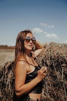 Portret van een mooie romantische jonge vrouw op het platteland bij zonsondergang