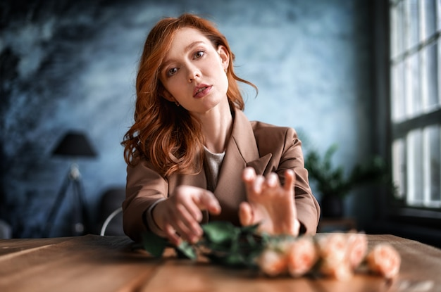 Portret van een mooie roodharige vrouw met bloemen aan de tafel zitten. de vrouw is gekleed in een bruin jasje.